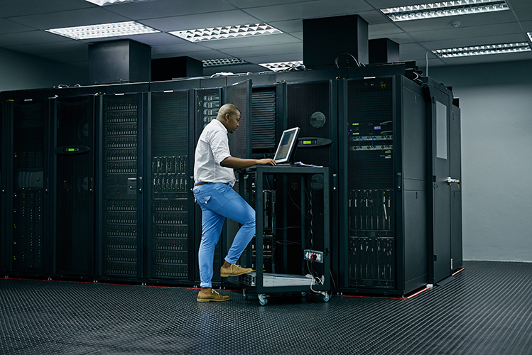 Shot of an IT technician using a computer while working in a data center